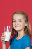 Portrait of young girl holding glass of milk against red background Royalty Free Stock Photography