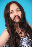 A portrait of a young girl holding hair mustache to her face Stock Photo