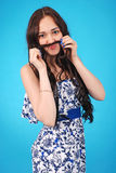 A portrait of a young girl holding hair mustache to her face Stock Images