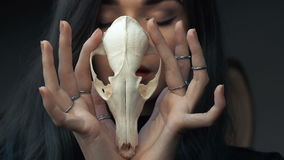 Portrait of a young girl holding a mysterious skull in the hands of a fox. Painted long hair. Portrait of a mysterious young girl holding a skull in the hands stock video footage