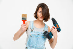 Portrait of young girl, holding painting brush and drill Stock Image