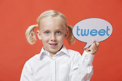 Portrait of a young girl holding tweet bubble against orange background Royalty Free Stock Photos