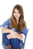 Portrait young girl in a jacket and blue jeans sitting on a chai Stock Images