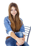 Portrait young girl in a jacket and blue jeans sitting on a chai. R, isolated on white Stock Image