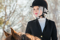 Portrait of young girl jockey riding a horse in winter forest Royalty Free Stock Image