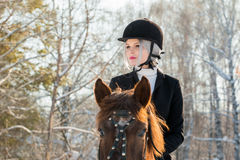Portrait of young girl jockey riding a horse in winter forest Stock Photo