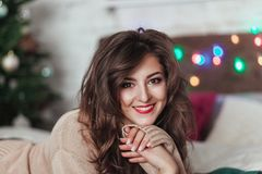 Portrait of a young girl in knitted cardigan in front of Christmas tree and blurred garland lies on the bed Royalty Free Stock Image