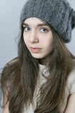 Portrait of a young girl in knitted warm hat. 
