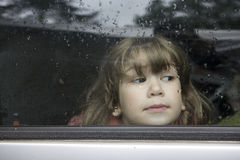 Portrait young girl looking through window Stock Photography