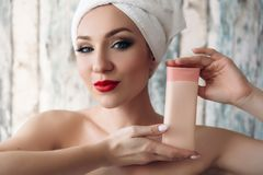 The portrait of a young girl made a spa procedure, enjoys the smoothness and health of her skin, reveals the cream that. Her cosmetician uses. The concept of Royalty Free Stock Images