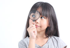 Portrait of young girl with magnifying glass stock photo