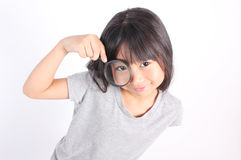 Portrait of young girl with magnifying glass . royalty free stock photography