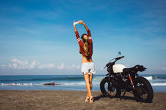 Portrait young girl on motorbike. Close up hipster portrait, young woman posing in the beach on custom vintage motorbike, driver, hipster, jeans, denim, ocean Stock Photo