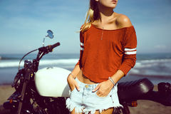 Portrait young girl on motorbike. Close up hipster portrait, young woman posing in the beach on custom vintage motorbike, driver, hipster, jeans, denim, ocean Stock Photos
