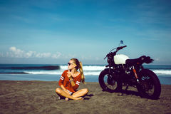 Portrait young girl on motorbike. Close up hipster portrait, young woman posing in the beach on custom vintage motorbike, driver, hipster, jeans, denim, ocean Royalty Free Stock Photos