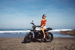 Portrait young girl on motorbike. Close up hipster portrait, young woman posing in the beach on custom vintage motorbike, driver, hipster, jeans, denim, ocean Royalty Free Stock Photography