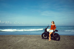 Portrait young girl on motorbike. Close up hipster portrait, young woman posing in the beach on custom vintage motorbike, driver, hipster, jeans, denim, ocean Stock Photography