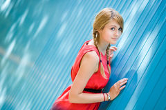 Attractive girl near the wall. Young blonde girl standing near the blue wall Royalty Free Stock Photos