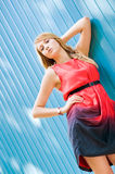 Young girl near the wall. Young blonde girl standing near the blue wall Stock Images