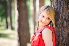 Pretty girl in park at summer time. Portrait of a young blonde girl near the tree in park Royalty Free Stock Photos