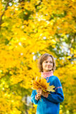Portrait of young girl in park with bunch of maple leaves Stock Photo