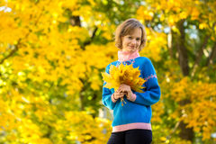 Portrait of young girl in park with bunch of maple leaves Stock Photos