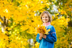 Portrait of young girl in park with bunch of maple leaves Stock Image