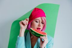 Young girl with pink hair in formal clothes of the 80s with a slice of watermelon and green paper. Portrait of a young girl with pink hair in formal clothes of royalty free stock photos
