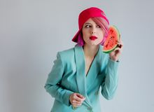 Young girl with pink hair in formal clothes of the 80s with a slice of watermelon. Portrait of a young girl with pink hair in formal clothes of the 80s with a stock photos