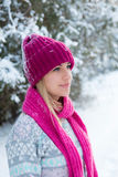 Portrait of young girl in pink hat and scarf in the winter fores. T Royalty Free Stock Photos