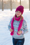 Portrait of young girl in pink hat and scarf. In the winter forest Royalty Free Stock Image