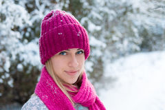 Portrait of young girl in pink hat and scarf. In the winter forest Royalty Free Stock Images