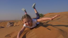 Portrait young girl playing with sand in hot desert during summer vacation. Joyful girl lying on sand dune in sunny desert and looking into camera stock video footage