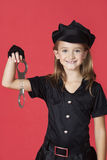 Portrait of young girl in police costume holding handcuffs against red background Royalty Free Stock Photography