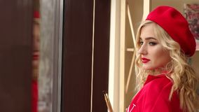 Portrait of a young girl in a red dress and hat near the window. Art. Close-up portrait of a young beautiful girl with red lipstick, in a red dress with tassels stock footage