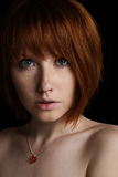 Portrait of a young girl with red hair and freckles with a pendant on the neck in the shape of a heart looking into the camera on. Dark background. Vertical Stock Photos