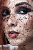 Portrait of young girl with red hair and ground coffee on the face. Photo with art makeup. Mature woman making cosmetic mask. Stock Image