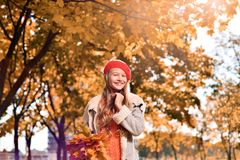 Portrait of young girl in red hat and autumn leaves in her hands royalty free stock image