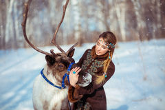 Portrait of a young girl with a reindeer in the winter Royalty Free Stock Images