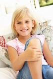 Portrait Of Young Girl Relaxing On Sofa Stock Photo