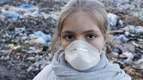 Portrait of a young girl in a respirator at the dump