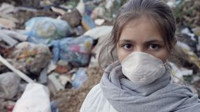 Portrait of a young girl in a respirator at the dump. Young girl in a white respirator at the garbage dump looks into the camera. Ecology concept. Slow motion stock video footage