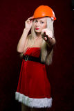 Portrait of a young girl in a Santa suit and helmet of the build Royalty Free Stock Image
