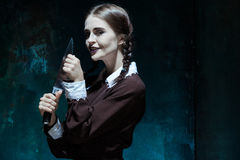 Portrait of a young girl in school uniform as killer woman. Portrait of a young girl with knife in school uniform as killer woman against school board . The Royalty Free Stock Images