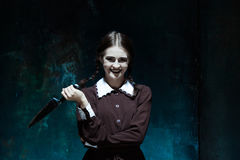 Portrait of a young girl in school uniform as killer woman Stock Images