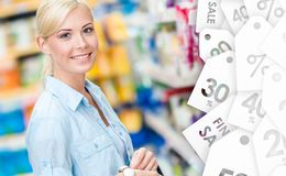 Portrait of young girl at the shop on sale. Portrait of young girl at the shop standing near the shelves with cosmetics. Sale time Royalty Free Stock Image