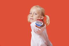 Portrait of a young girl showing vote badge over pink background Stock Photo