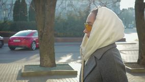 Portrait of a young girl on the side, she walks around the city in a coat and glasses stock footage
