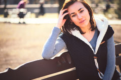 Portrait of young girl sitting on a bench Stock Images