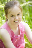Portrait Of Young Girl Sitting In Field Royalty Free Stock Image